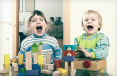Emotional sibling playing in  blocks in home